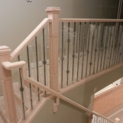 Unpainted wooden handrail looking downstairs.