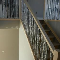 Unpainted simple handrail with metal spindles.