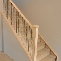 Unpainted handrail with metal spindles.
