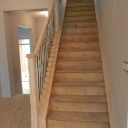 Looking upstairs at unfinished stairs and handrails.