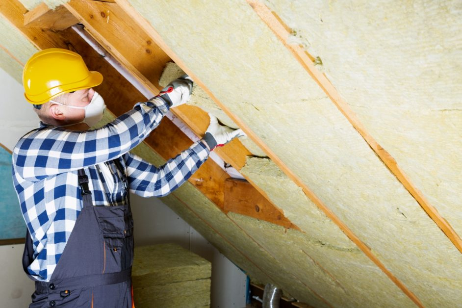construction worker using PPE installing insulation in roof