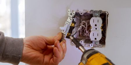 An image of a residential electrician in Jackson, TN, making a repair.
