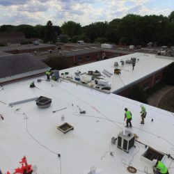 Roofers working on a commercial roofing project - Denali Roofing