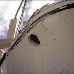 An image of damage to the underside bow of a yacht with a large hole, dents, and scratches.
