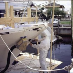 An image of a craftsman repairing damage on the outside of a yacht.