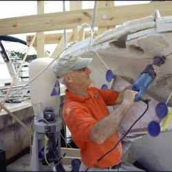 An image of a Dennis Boatworks' expert craftsman repair damage on the outside bow of a yacht.