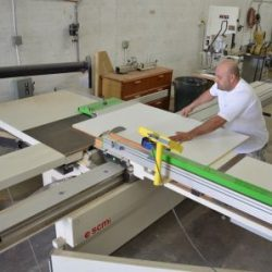 An image of an employee cutting a wooden board with a table saw at Dennis Boatworks.