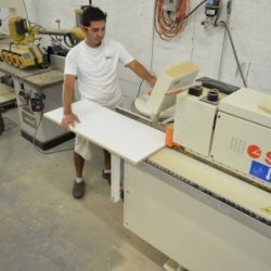 An image of an employee of Dennis Boatworks carefully measuring and precisely cutting a wood plank.