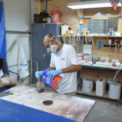 Image of an employee of Dennis Boatworks mixing varnish.