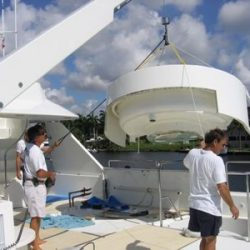 A photo of a large jacuzzi being lowered onto the yacht to be installed during a remodeling project.