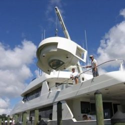 An image of two people standing on the top deck of a Dennis Boatworks yacht client.