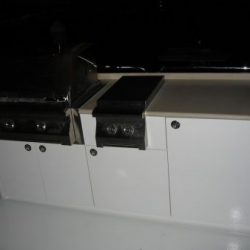 A photo of a stainless steel barbecue grill built into an on deck kitchen cabinet.