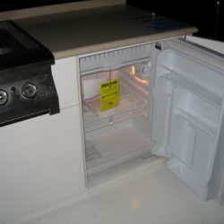 An image of a mini fridge masked as a cabinet beneath a countertop.