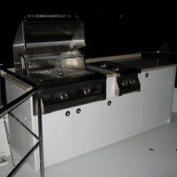 An image taken at night of a stainless steel grill built into the countertop of an on deck cabinet.