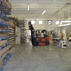 An image of the inside of the Dennis Boatworks workshop with an employee driving a forklift.
