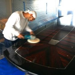 An image of a master crafter polishing a custom wood table made by Dennis Boatworks.