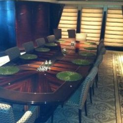 An image of a custom interior below deck dining room with a 12-person dining table built by Dennis Boatworks.