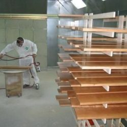 An image of a Dennis Boatworks employee staining wood.