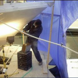 Photo of a master craftsman for Dennis Boatworks working on the bough of the ship.