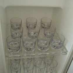 Photo of custom acrylic shelving for protective dish storage by Dennis Boatworks.