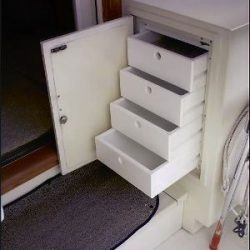 Image with custom cabinet featuring four pull out drawers for optimal storage space designed by Dennis Boatworks.