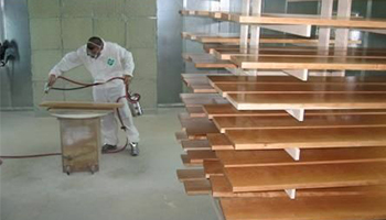 An image of an employee staining wood for Dennis Boatworks.