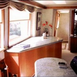 An image of spacious, custom interior with well-lit windows and wooden furnishing made by Dennis Boatworks.