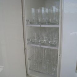 Image of shelving with custom dish storage solutions created by Dennis Boatworks.