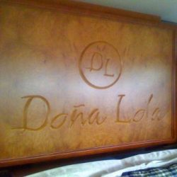 Image of a large, polished, hand carved wooden panel decorating a wall inside a yacht.