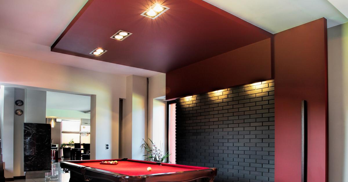 Recessed lighting against brick in a billiard room.