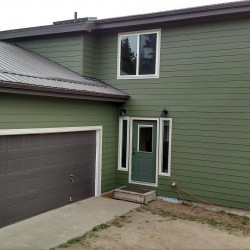 View of home's garage with deep green lap siding - DJK Construction