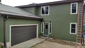 View of home's garage with deep green lap siding - DJK Construction