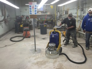 Starting proper garage floor coating with sanding and vacuuming.