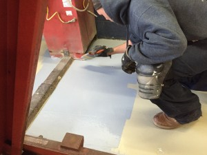 A blue garage floor coating in being applied.