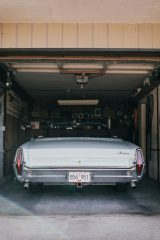 An image of a garage with a blue vintage car inside it.
