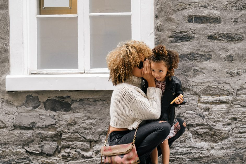 An image of a mother and daughter standing outside a home.