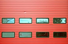 An image of a red garage door with windows.