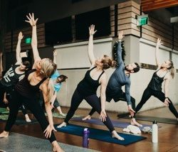 A group of students in yoga class at Duality Fit in Sloan Lake practices their triangle pose.