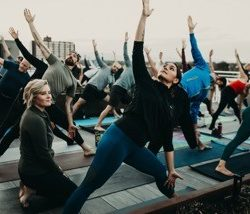 Our Duality Fit instructor Nattiel leads one of our yoga classes and helps students with their form. Become a yogi yourself at Duality Fit in Sloan Lake.