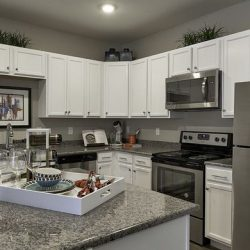 Open kitchen with white cabinets and stone island - Elements at Prairie Center
