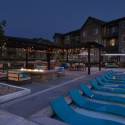 Apartment complex with lounge chairs in the water, fire pit, and seating area - Elements at Prairie Center