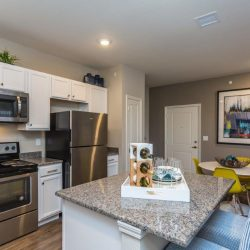 Kitchen with stone island and white cabinets in an apartment home - Elements at Prairie Center