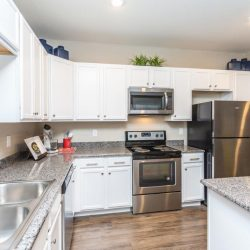 Apartment home kitchen with white cabinets and stainless steel appliances - Elements at Prairie Center