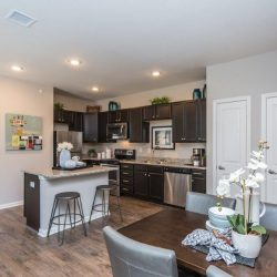 Kitchen with island and dining table in an apartment rental - Elements at Prairie Center