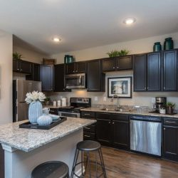 Apartment home kitchen with dark cabinets and island - Elements at Prairie Center