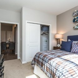 Bedroom with closet and door to living space in an apartment - Elements at Prairie Center