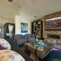 Living room-like apartment clubhouse with fireplace, couches, and arcade games - Elements at Prairie Center