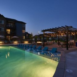 Apartment complex outdoor area with pool, pergola, and lounge chairs - Elements at Prairie Center