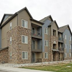 Apartment complex with stone siding and balconies - Elements at Prairie Center