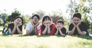 A family of five lies in their bellies on the grass, faces rested in their palms, and makes silly faces at the camera.